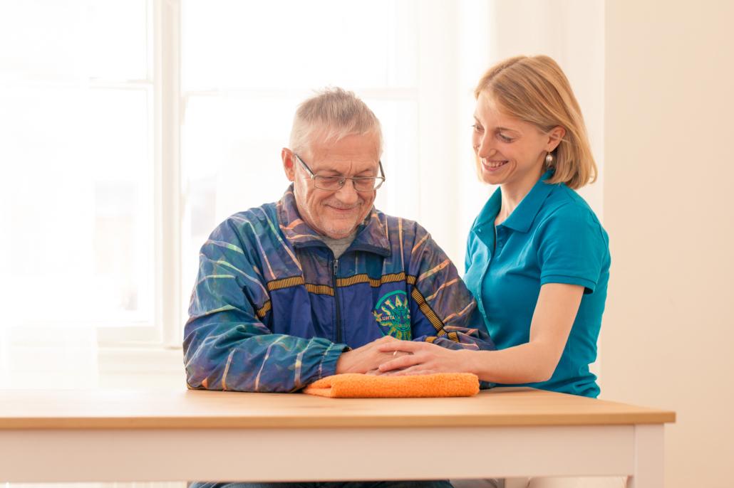 Ein männlicher Patient und die Therapeutin Eva-Maria Möseneder bei der Ergotherapie